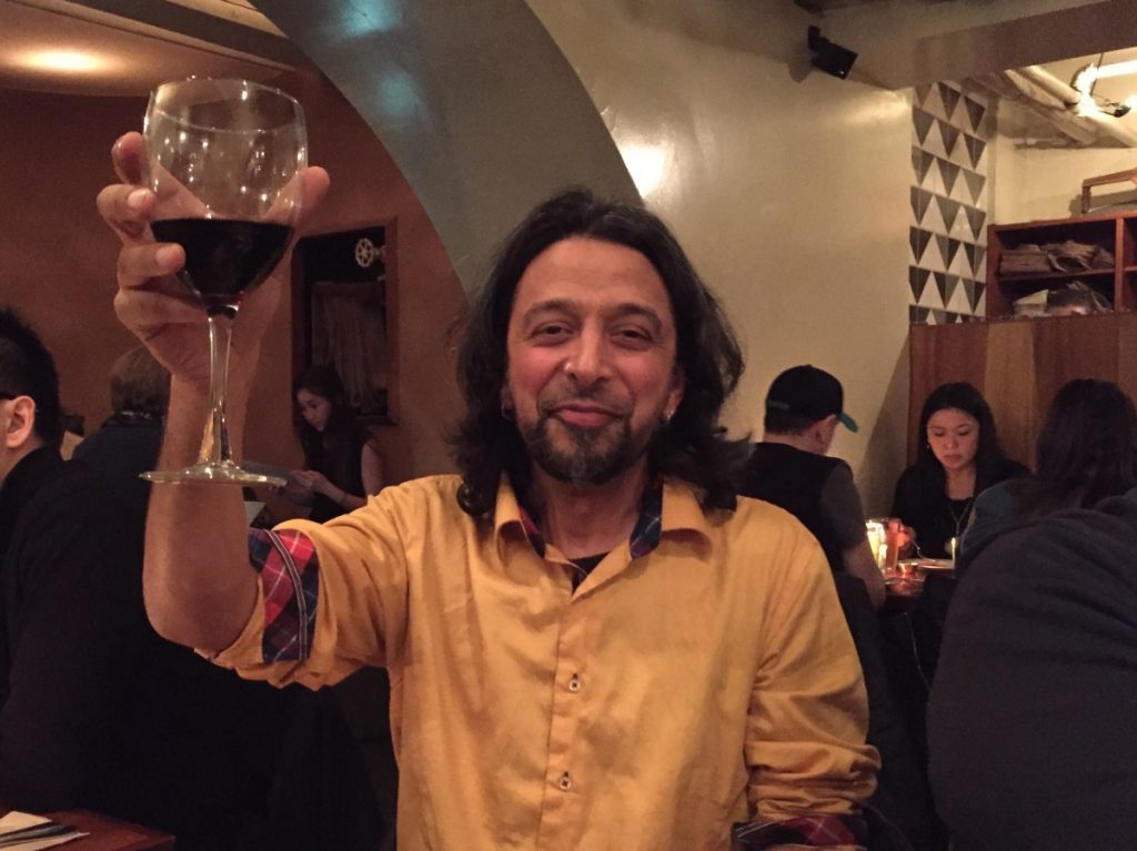 Shiraz Dindar of Kanopi raising a glass of wine in a toast at dinner.