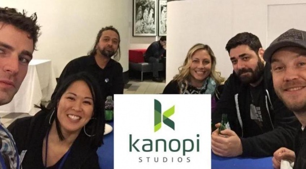 Photo of Kanopi employees smiling, with the Kanopi logo in the center.