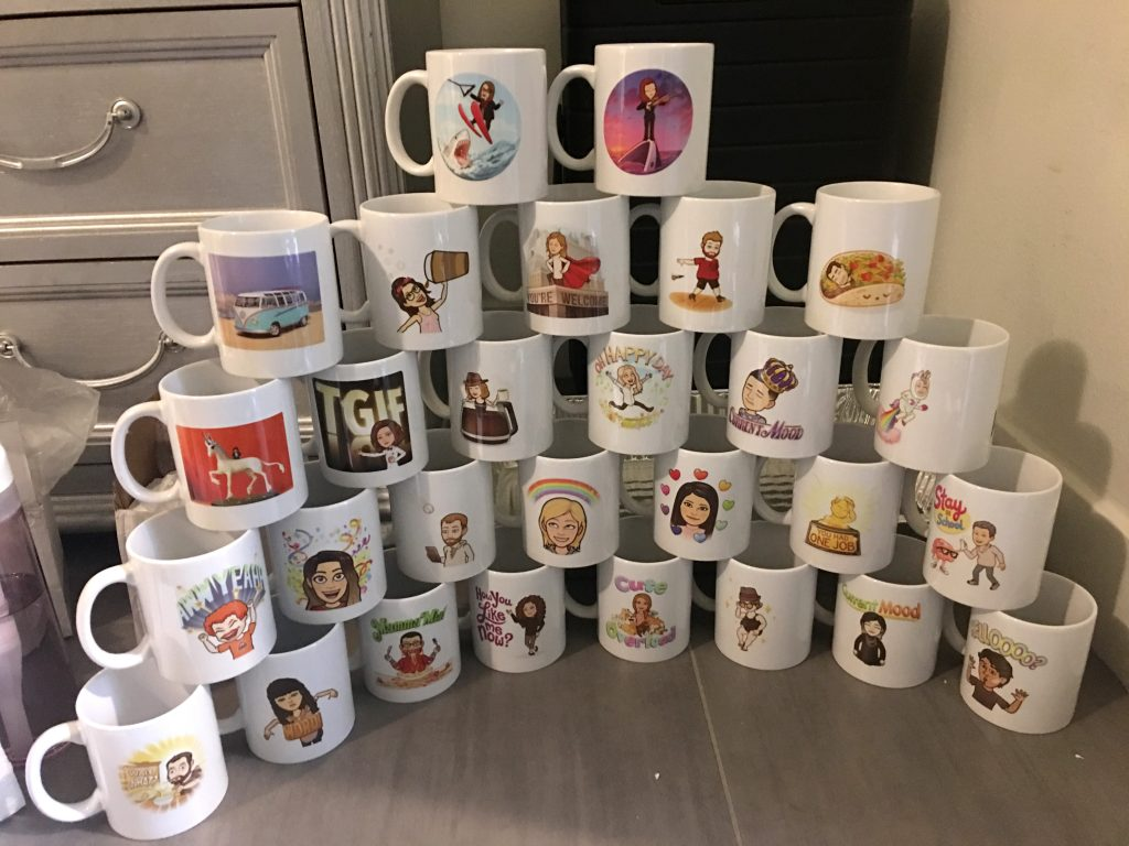 Shot of white mugs stacked in a pyramid, each personalized with a bitmoji for that person.