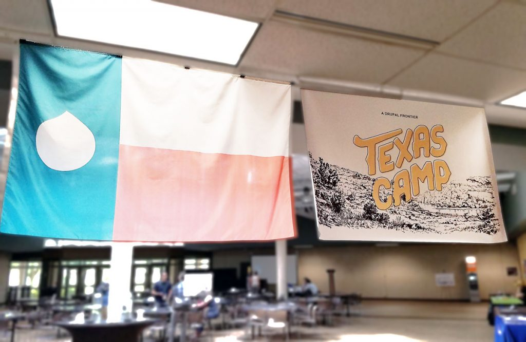 The Texas flag with a Drupal drop instead of a star, and the Texas Camp 2017 sign hanging from a ceiling