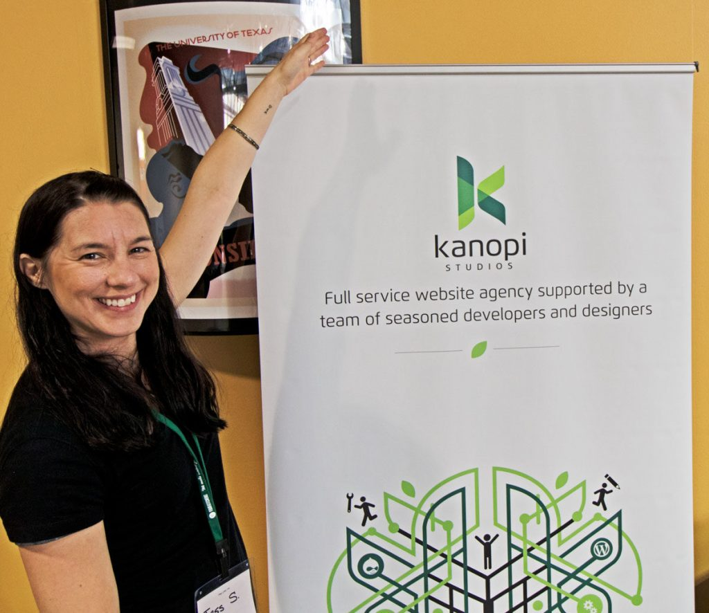 Happy woman with arms open, standing next to a conference sign that says 'Kanopi Studios'