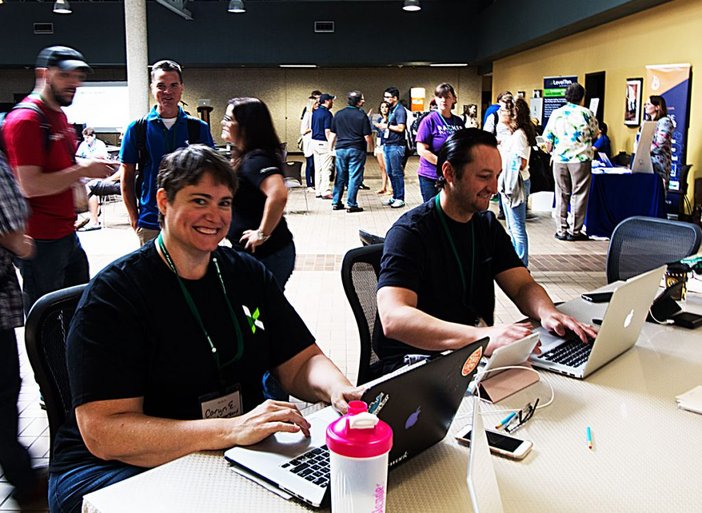 A happy woman and man using laptops at a table, surrounded by happy, chatting camp attendees.