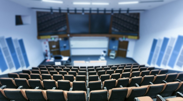 A large classroom in a higher education setting: there are many seats facing a large video screen and dry-erase board.