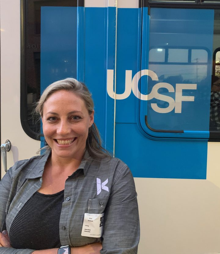 Anne Stefanyk smiling in front of a UCSF logo on the side of a bus